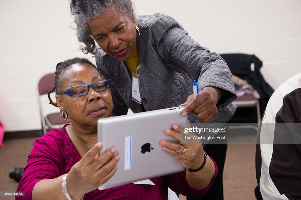 Senior, Rosa Lassiter, 62, left, works with Instructor, Emma Ward, to use the camera feature of the iPad. AARP Foundation and Family Matters partnered in a pilot program, Connect To Community, teaching low-income seniors (mostly from Ward 2) how to use the internet on an iPad to combat isolation and increase social activity. They chose seniors who have no previous experience with the internet or computers. Comcast wires their home for wi-fi at a discounted rate for one year. If they complete the 6-month course, they keep the iPads.