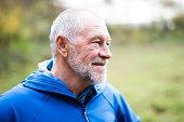 Close up of senior runner in nature. Man in blue sweatshirt, resting, smiling.