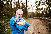 Senior runner in nature. Man with smartphone and earphones, adjusting settings on armband for phone. Listening music or using a fitness app. Using phone app for tracking weight loss progress, running