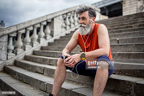 Senior runner resting on steps
