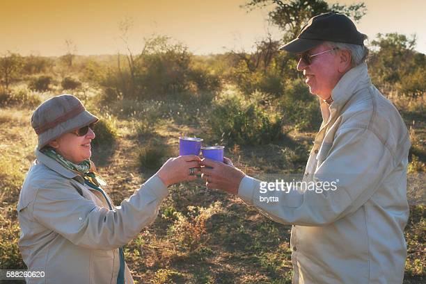 Senior safari guests toasting   in the bush,South Africa