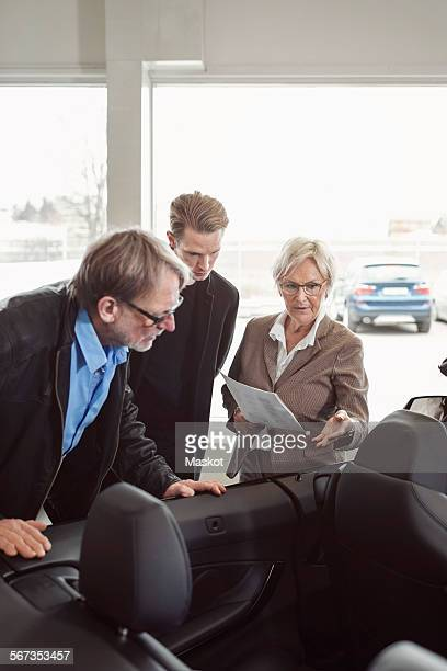 Senior saleswoman explaining car features to family at store