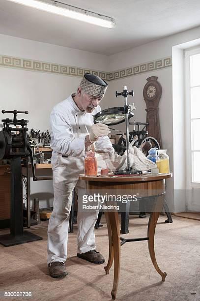 Senior sculptor colouring a Jesus Christ statue at workshop, Bavaria, Germany