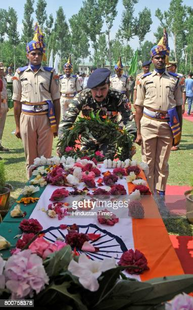 A senior security force officer lays a wreath on the coffin containing the body of slain paramilitary Central Reserve Police Force SubInspector Sahab...