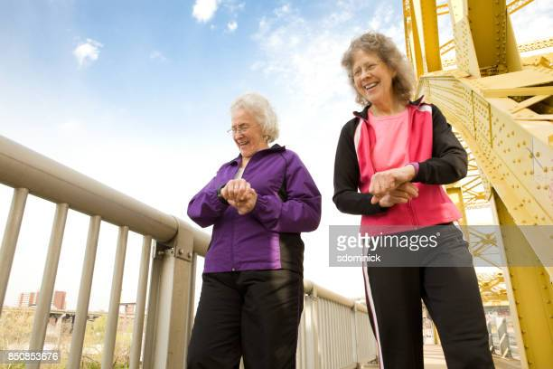 Senior Sisters Laughing And Walking Together