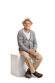 Senior sitting on a cube and looking at the camera isolated on white background