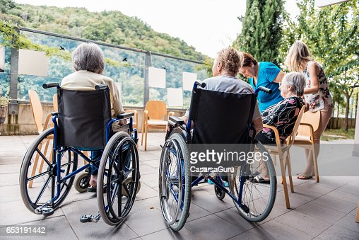 Senior Socializing Outside In The Retirement Home : Stock-Foto