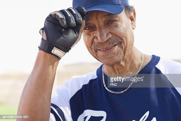 Senior softball player tipping baseball cap, close up, portrait