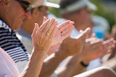Senior spectators clapping at an event