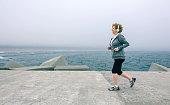 Senior sportswoman with headphones running by sea pier