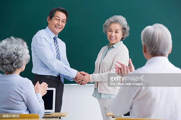 Senior student having a handshake with teacher in classroom