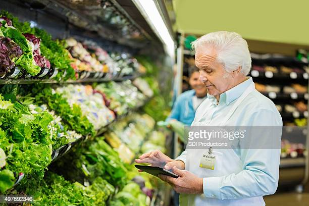 Senior supermarket manager or employee taking inventory in produce section