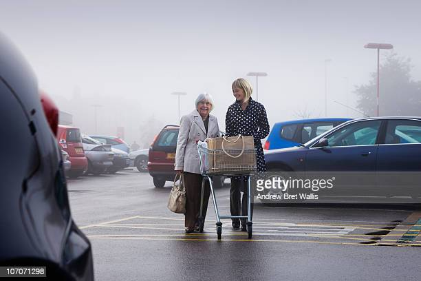 senior supermarket shopper with female volunteer
