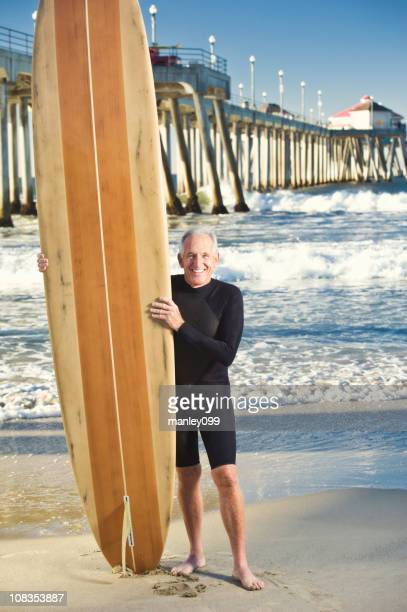 senior surfer laughing with surfboard