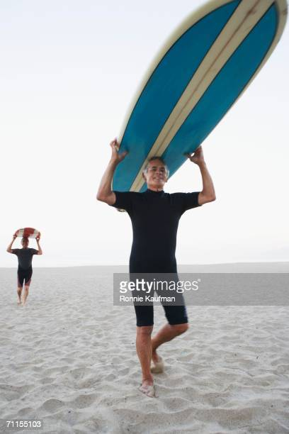 Senior surfers carrying their boards at the beach