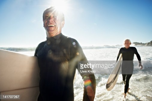 Senior Surfers on beach, close up