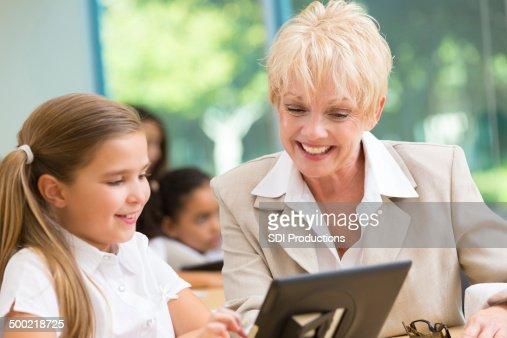 Senior teacher explaining assignemt to student with digital tablet