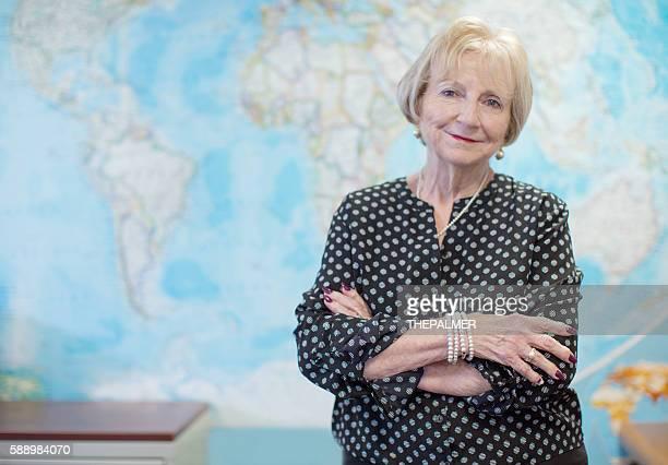 Senior teacher in front of map