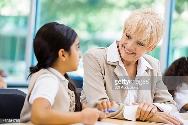 Senior teacher tutoring student in private school classroom