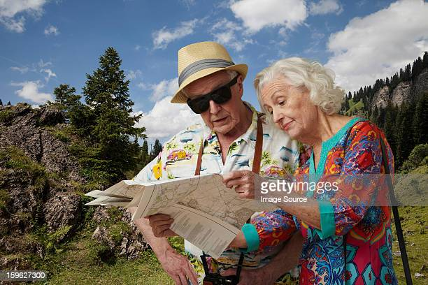 Senior tourist couple looking at map