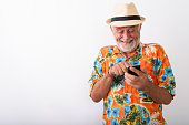 Studio shot of happy senior bearded tourist man smiling and giggling while using mobile phone against white background horizontal shot