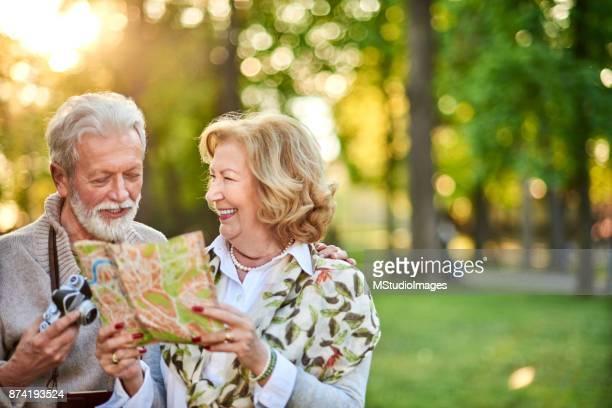 Seniora turister med karta i naturen