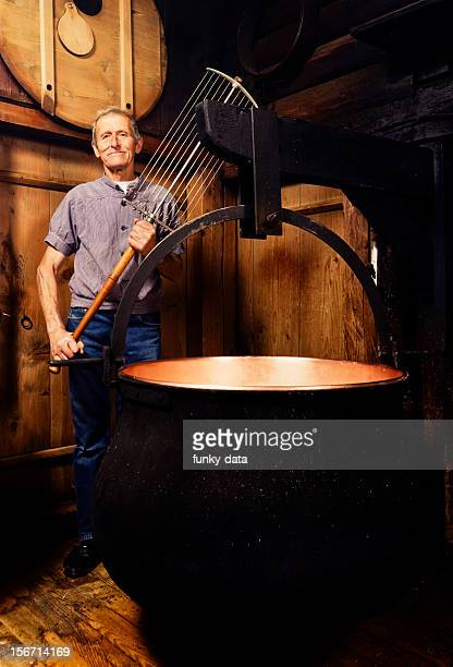 Senior traditional Alpine cheese maker holding a Swiss harp