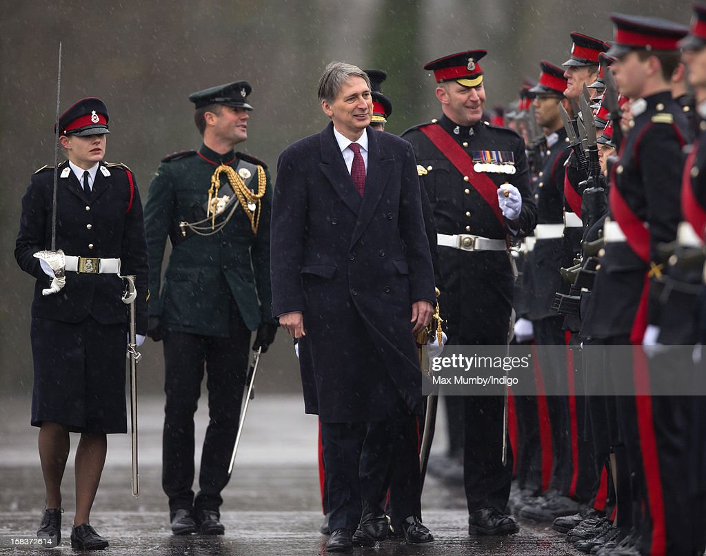 Senior Under Officer Sarah Hunter-Choat (L) accompanies Secretary of State for Defence Philip Hammond as he inspects the Officer Cadets whilst representing Queen Elizabeth II during the Sovereign's Parade at the Royal Military Academy Sandhurst on December 14, 2012 in Sandhurst, England. The parade marks the completion of 44 weeks of training for 200 young people who will be commissioned into the British Army and the armies of 13 overseas countries. Senior Under Officer Sarah Hunter-Choat became the fourth woman in the Royal Military Academy's history to receive the prestigious Sword of Honour which is awarded to the best Officer Cadet on the course.