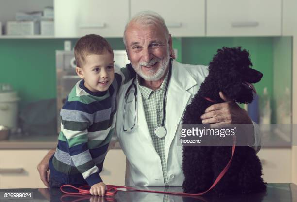 Senior Veterinarian Treating a Young Boy's Poodle