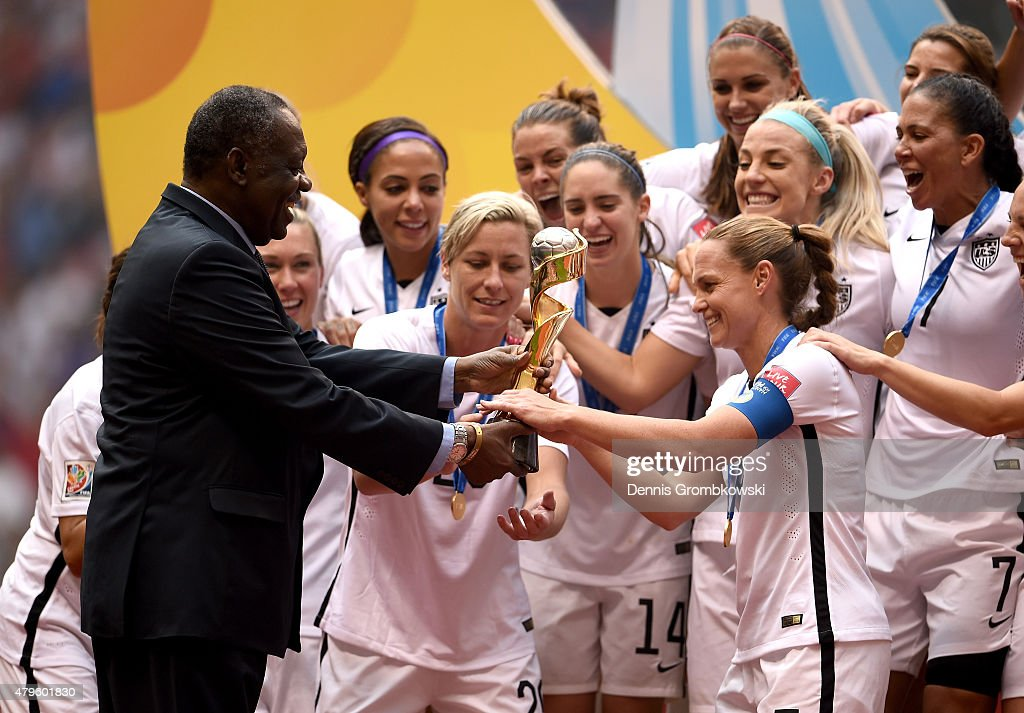 Senior Vice President Issa Hayatou of Africa hands the Wold Cup Trophy to Abby Wambach #20 and Christie Rampone #3 of the United States as they celebrate after winning the FIFA Women's World Cup Canada 2015 5-2 against Japan at BC Place Stadium on July 5, 2015 in Vancouver, Canada.