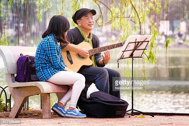 Senior Vietnamese man sings song with guitar in park