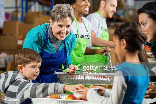 Senior volunteer and child volunteering together at soup kitchen