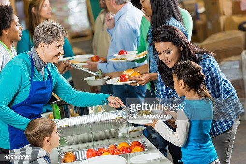 Senior volunteer serving healthy meal to family at soup kitchen