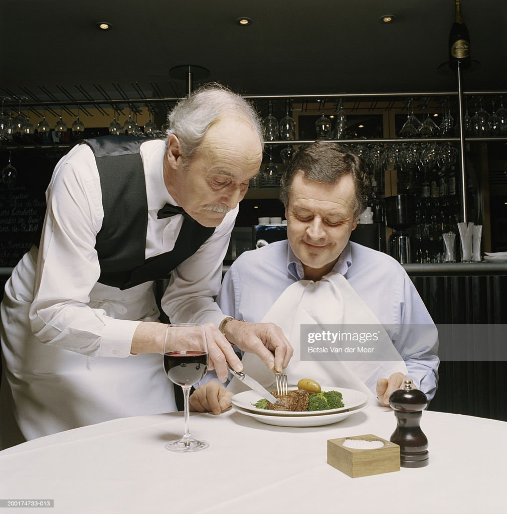 Senior waiter cutting mature man's food on plate in restaurant : Stock Photo