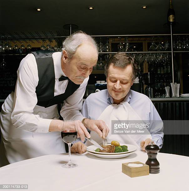 Senior waiter cutting mature man's food on plate in restaurant