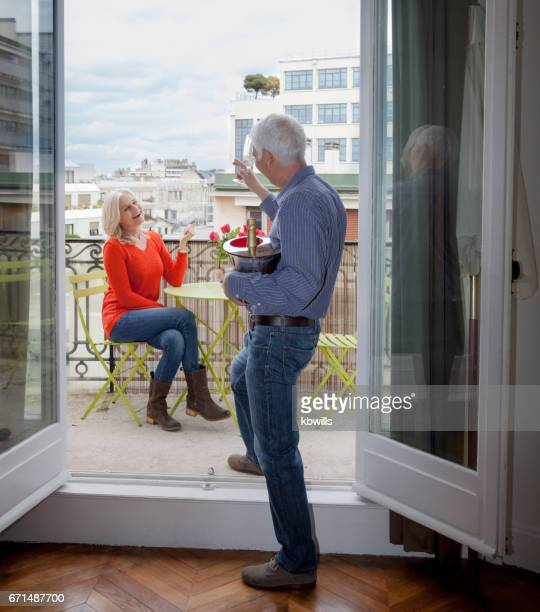 senior white haired man surprizes mature blonde lady with champagne and roses on balcony at open french windows