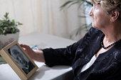 Photo of senior widow reminiscing her dead husband