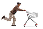 Full length profile shot of a senior with 3D glasses running and pushing an empty shopping cart isolated on white background