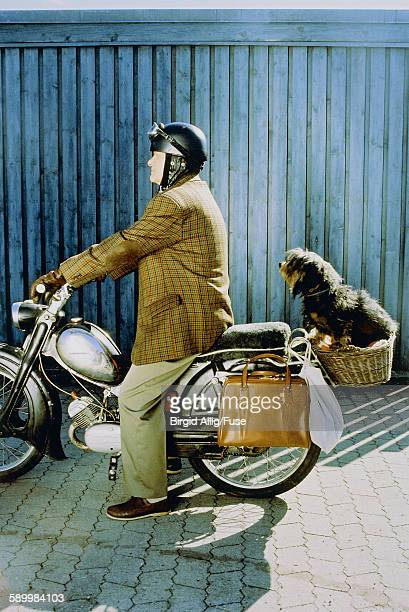 Senior with little dog on a motorbike