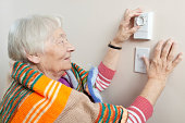 Senior woman saving energy by dressing warm and adjusting her thermostat.