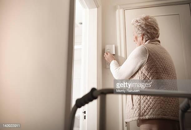 Senior woman adjusting thermostat in hallway