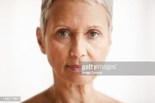 Senior woman against white background, portrait