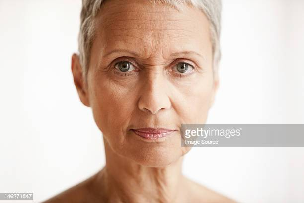 Senior woman against white background, portrait