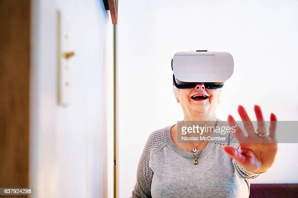 Senior woman amazed at using VR helmet