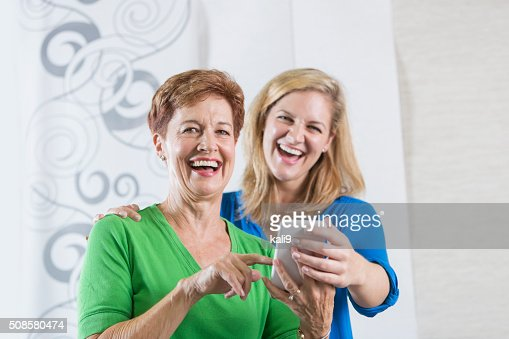 Senior woman and adult daughter laughing at phone : Stockfoto