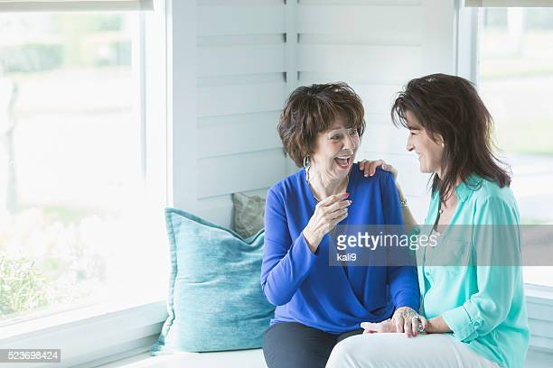 Senior woman and adult daughter laughing together