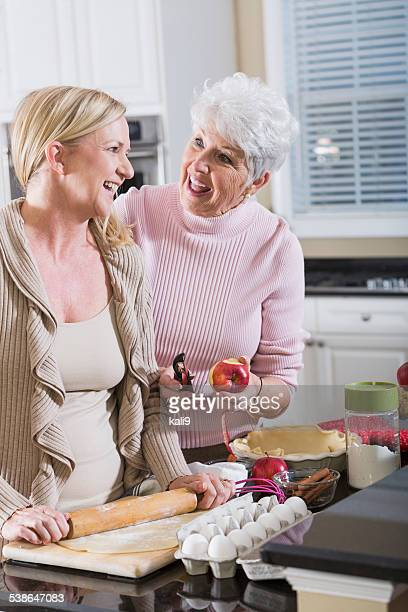 Senior woman and adult daughter making apple pie
