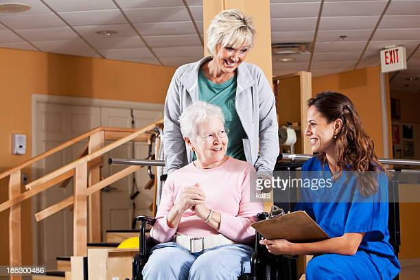 Senior woman and adult daughter talking to physical therapist