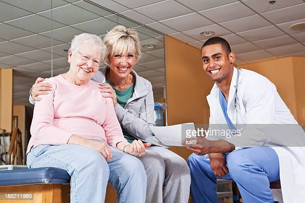Senior woman and adult daughter with physical therapist