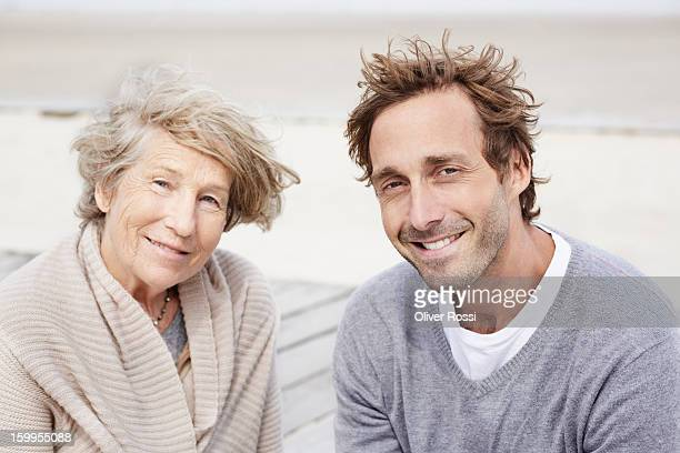 Senior woman and adult son on the beach, portrait